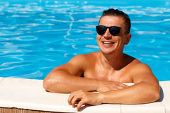 Close up portrait of attractive young man  in sunglasses resting. On edge of swimming pool Stock Photo