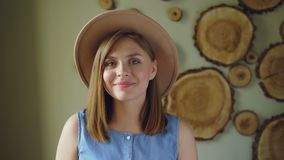 Close-up portrait of attractive young woman with blond hair wearing trendy hat and denim top looking at camera and. Smiling. Modern people and positive emotions stock video footage