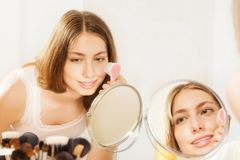 Attractive young woman using skin-cleaning brush. Close-up portrait of attractive young woman massaging her cheeks, using a skin-cleaning brush, seen in makeup stock photo