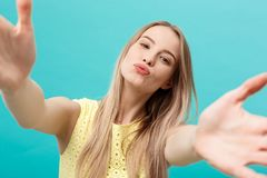 Close-up portrait of attractive young woman stretching her arms, wants to hug and kiss you. Isolated on blue background. Close-up portrait of attractive young Royalty Free Stock Photo