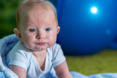 Close-up portrait of the baby. Blue ball on background Royalty Free Stock Photography