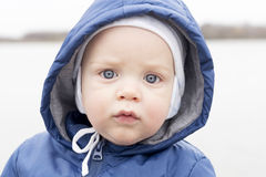 Close-up portrait of baby boy looking at camera. Cute infant boy in a hat and a hood. Outdoor shot.  Royalty Free Stock Photography