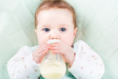 Close up portrait of a baby girl with a milk bottle lying on a green knitted blanket Royalty Free Stock Photography