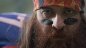 Close up portrait of a bearded american football player with long hair and beard in sports equipment puts black paint on stock footage