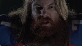 Close up portrait of a bearded american football player with long hair and beard in sports equipment shouting looking in. Camera in blinking light. The man stock video footage