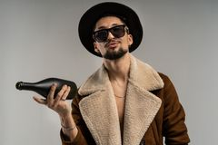 Close up portrait of a bearded hipster man in sunglasses in a brown jacket and black hat royalty free stock photos