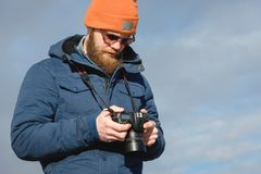 Close-up portrait bearded male photographer in sunglasses with dslr camera in his hands looks at the photos on the royalty free stock photo