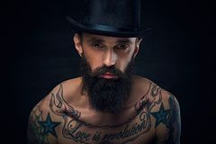 Tattooed bearded male in cylinder hat. Close up portrait of bearded male in top hat with tattoos on his chest over dark background Royalty Free Stock Photos
