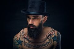 Tattooed bearded male in cylinder hat. Close up portrait of bearded male in top hat with tattoos on his chest over dark background Stock Photo