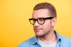 Close up portrait of bearded man in glasses with serious express. Ion looking to the side over yellow background Royalty Free Stock Image
