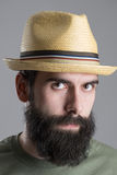 Close up portrait of bearded man wearing straw hat with intense look at camera. Stock Photos