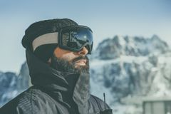 Close-up portrait of bearded young snowboarded in sunglass mask, at the ski resort on the background of mountains and royalty free stock photo