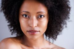 Close up beautiful african woman with curly hair and naked shoulders. Close up portrait of beautiful african woman with curly hair and naked shoulders Royalty Free Stock Image