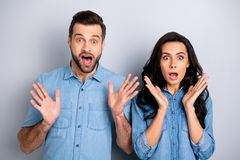 Close up portrait beautiful amazing she her he him his couple lady guy look eyes full fear hands arms raised up oh no. Expression wear casual jeans denim shirts royalty free stock photography