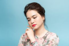 Close up portrait of a beautiful Asia girl while standing on blue background royalty free stock photos