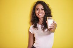 Beautiful asian woman offering a glass of fresh milk. Close up portrait of beautiful asian woman offering a glass of fresh milk on yellow background Stock Photos