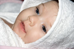 Close-up portrait of a beautiful baby. Girl covered with white bath towel Stock Images