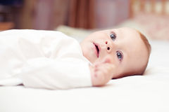 Close-up portrait of beautiful baby lying on bed Stock Images