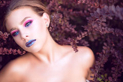Close up portrait of beautiful blue-eyed model with bright fashion make up posing in purple barberry bushes with air of detachment royalty free stock photography