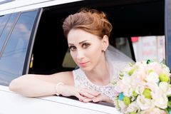 Close-up portrait of a beautiful bride aged beside her wedding bouquet in the window of a wedding car. royalty free stock image
