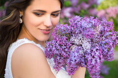 Close up portrait of beautiful bride with big bouquet of lilac Stock Image