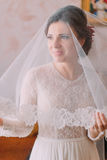 Close-up portrait of beautiful bride in wedding dress with long veil posing indoors in dressing room Royalty Free Stock Photography