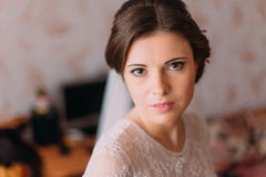 Close-up portrait of beautiful bride in wedding dress posing indoors in dressing room Royalty Free Stock Photos
