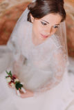 Close-up portrait of beautiful bride in wedding gown sitting on carpet and holding cute floral boutonniere Stock Images