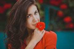 Close-up portrait of beautiful brunette woman with red rose in her lips. Toned image Stock Photography