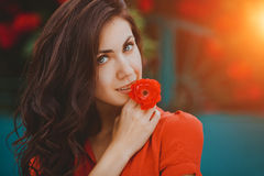 Close-up portrait of beautiful brunette woman with red rose in her lips. Toned image Stock Photos