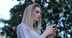 A close-up portrait of a beautiful caucasian girl with bright eyes typing on her cell phone and smiling outdoors. Side stock video