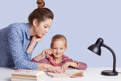 Close up portrait of beautiful Caucasian woman helping her doughter to do school homework, female with bunch on head, wearing royalty free stock image