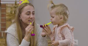 Close-up portrait of beautiful Caucasian woman and little cute girl playing with party whistles at home. Young mother in stock video footage