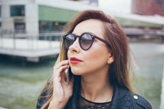 Close-up portrait of a beautiful Caucasian woman with red lipstick. Female is having mobile phone conversation, discussing work tasks. Young female in hipster Royalty Free Stock Photography