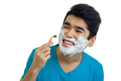 Close-up portrait of a beautiful cheerful guy who caused the foam on a beard and shaves Stock Photography