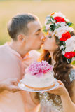 Close-up portrait of beautiful couple kising outdoors holding cake decorated with pink flowers Royalty Free Stock Photos