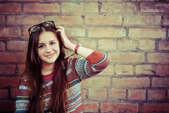Close up portrait of a beautiful cute teen girl smilling. Near the brick wall Stock Photo