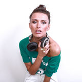 Close up portrait of beautiful dj woman with black. Hair in green shirt, white jeans poses holding earphones decorated rhinestones and diamonds on white Royalty Free Stock Photo
