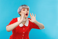 Close up portrait of beautiful dollish girl with short light violet hair wearing red dress shouting over blue background Royalty Free Stock Photo