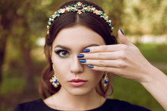 Close-up portrait of beautiful fashion woman with bright purple manicure, stylish makeup. The girl is holding a hand. Near the face, covering one eye. Manicure royalty free stock photo