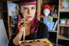 Close up portrait of beautiful female artist with purple hair. And dirty hands with different paints on them, holding paint brushes near her face and eyes stock photos