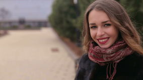 Close-up portrait of a beautiful girl in black coat walking in park. stock video