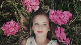 Close up portrait beautiful girl lies in the field looks at the camera stock footage