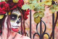Close up portrait beautiful girl in makeup traditional Mexican Calavera sugar skull on the background of an iron fence with spikes. Day of the dead. Halloween stock photo