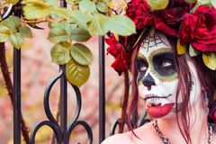 Close up portrait beautiful girl in makeup traditional Mexican Calavera sugar skull on the background of an iron fence with spikes. Day of the dead. Halloween stock images