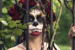 Close up portrait beautiful girl in makeup traditional Mexican Calavera sugar skull on the background of an iron fence with spikes. Day of the dead. Halloween stock image