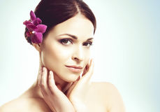 Close-up portrait of a beautiful girl with an orchid flower in h Stock Photos