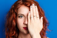 Portrait of a beautiful girl, with red hair examining eyes, closing her eyes with her hand on a blue bright background stock image