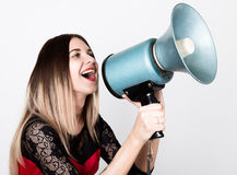 Close-up portrait of a beautiful girl in a red dress with lace sleeves, she yells into a bullhorn. Public Relations Royalty Free Stock Photos