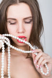 Close-up portrait of a beautiful girl with red lips, holding a pearl necklace. mouth open, pearls touches her lips. Red Stock Image